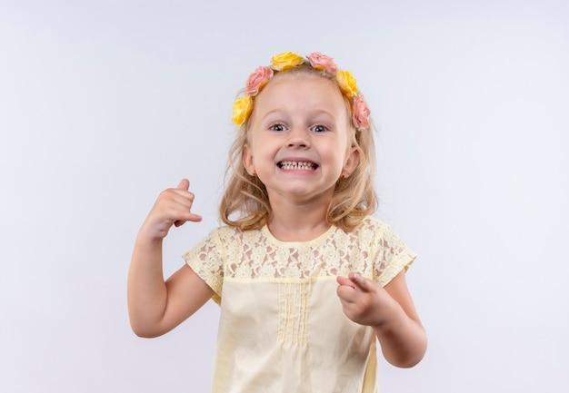Een vrolijk schattig klein meisje met een geel shirt in een bloemenhoofdband die 'bel me' gebaar toont terwijl ze op een witte muur wijst