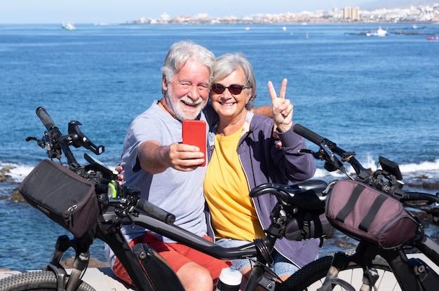 Een vrolijk senior koppel dat geniet van een excursie op zee met hun fietsen, horizon aan zee. actieve mooie gepensioneerden genieten van een gezonde levensstijl met behulp van mobiele telefoon voor een selfie
