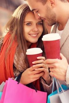 Een vrolijk stel dat met koffie in het winkelcentrum winkelt