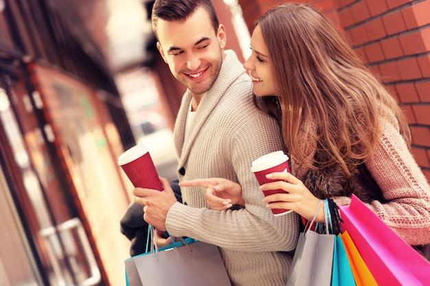 Een vrolijk stel etalages in het winkelcentrum met koffie