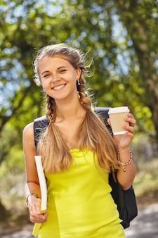 Een vrolijk studentenmeisje dat buiten koffie houdt