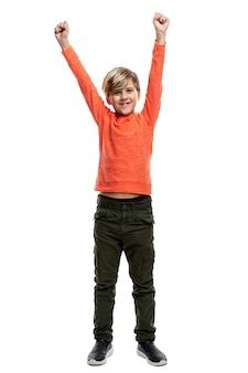 Een vrolijke 9-jarige jongen in een oranje trui en een groene broek hief zijn handen op.