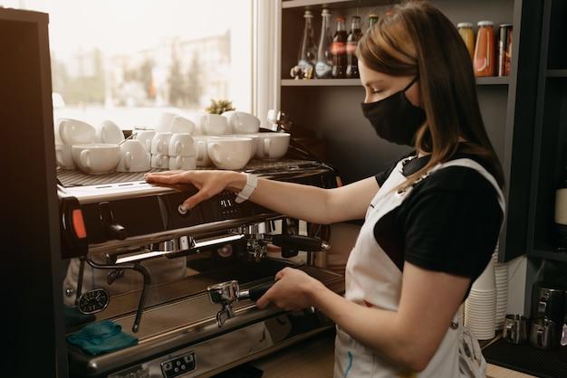 Een vrolijke barista in een medisch masker werkt met een koffiezetapparaat