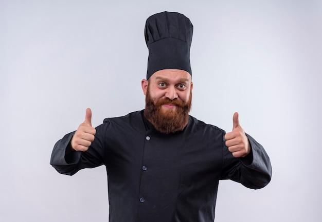 Een vrolijke, bebaarde chef-kok in zwart uniform duimen opdagen terwijl hij op een witte muur kijkt
