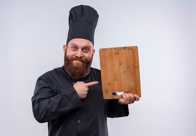 Een vrolijke bebaarde chef-kok man in zwart uniform wijzend op een houten keukenbord op een witte muur