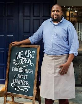 Een vrolijke bedrijfseigenaar die zich met open bord bevindt