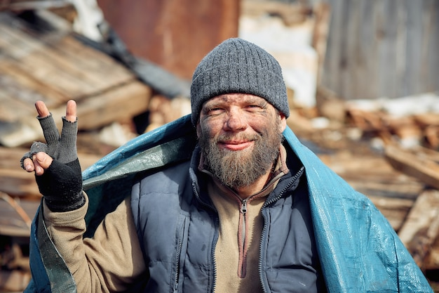 Een vrolijke dakloze en werkloze man in de ruïnes