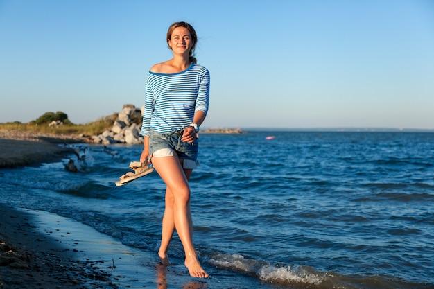 Een vrolijke donkerharige vrouw lacht, loopt langs het strand, schopt tegen de golven, sproeit veel en geniet van de felle zon op een zomerse dag. concept zomervakantie op zee en live style
