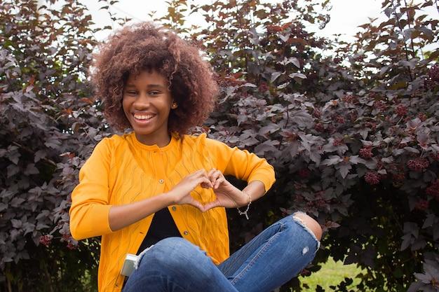 Een vrolijke en jonge afro-amerikaanse vrouw toont een hart met haar handen