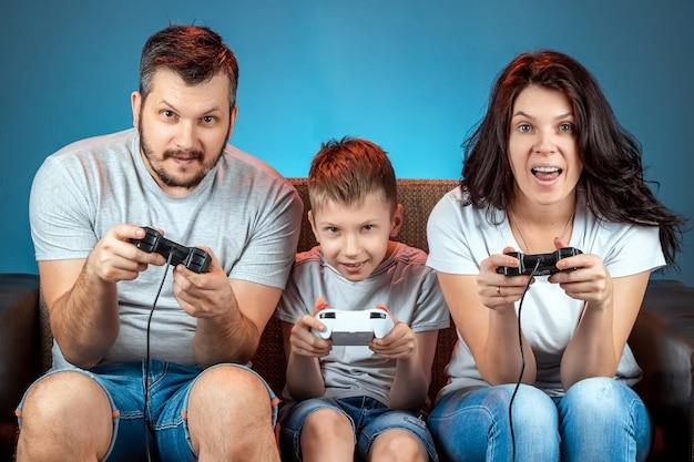 Een vrolijke familie, vader, moeder en zoon spelen op de console, videogames, reageren emotioneel zittend op de bank. vrije dag, entertainment, vrije tijd, tijd samen doorbrengen.