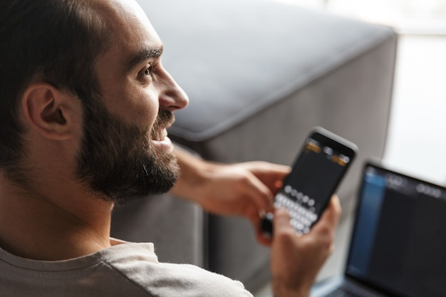 Een vrolijke gelukkige jonge man binnenshuis thuis op de bank met behulp van laptopcomputer chatten via de mobiele telefoon.
