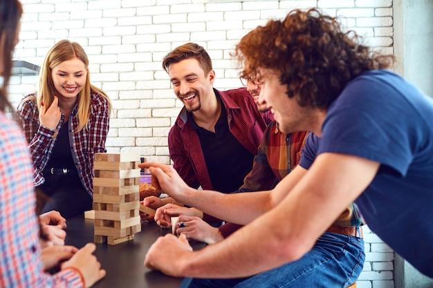 Een vrolijke groep jonge mensen speelt bordspellen in de kamer.