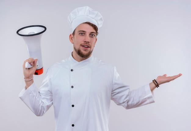 Een vrolijke jonge bebaarde chef-kok man met een wit fornuis uniform en hoed met megafoon met open hand terwijl hij op een witte muur kijkt