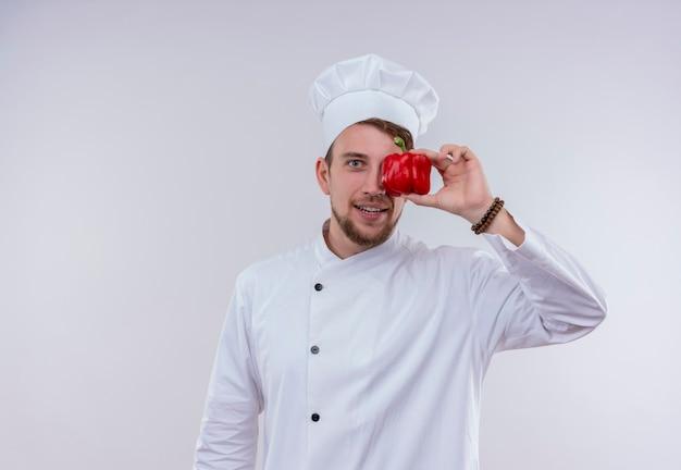 Een vrolijke jonge, bebaarde chef-kokmens die een wit fornuisuniform draagt en een hoed die rode paprika houdt en op een witte muur kijkt