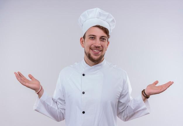 Een vrolijke jonge, bebaarde chef-kokmens in wit fornuisuniform en hoed die zijn handen vriendelijk opent terwijl hij op een witte muur kijkt