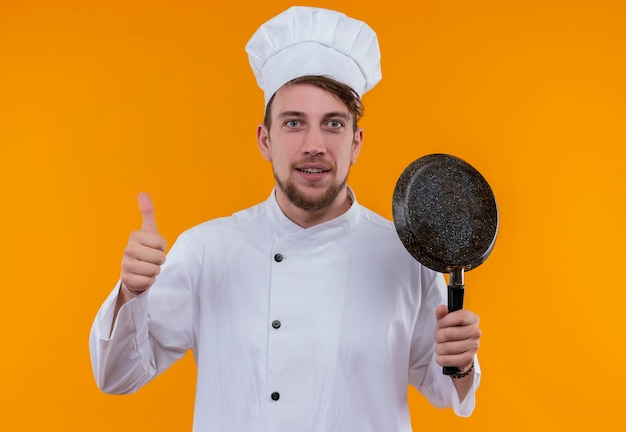 Een vrolijke jonge, bebaarde chef-kokmens in wit uniform die koekenpan houdt en duim toont terwijl hij op een oranje muur kijkt