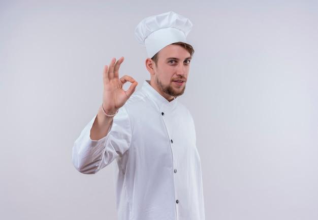 Een vrolijke jonge bebaarde chef-kokmens in wit uniform die ok gebaar op een witte muur toont