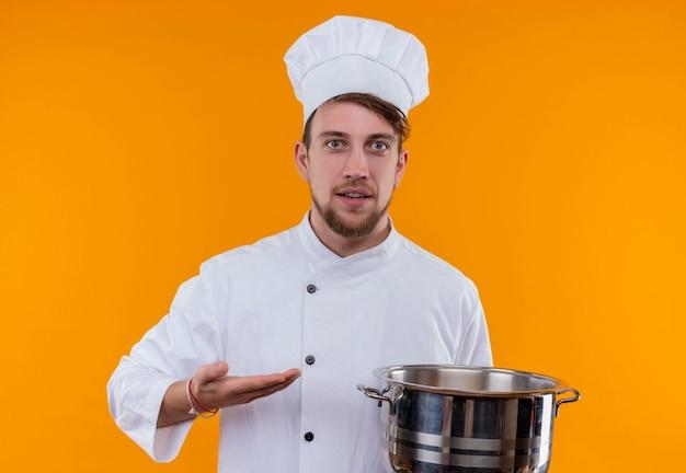 Een vrolijke jonge, bebaarde chef-kokmens in wit uniform die sauspan toont terwijl hij op een oranje muur kijkt