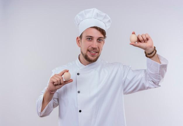 Een vrolijke jonge, bebaarde chef-kokmens met een wit fornuisuniform en een hoed die glimlacht en eieren vasthoudt terwijl hij op een witte muur kijkt