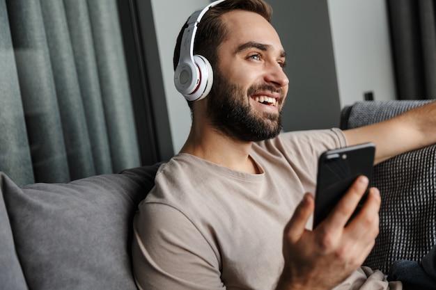 Een vrolijke jonge gelukkig man binnenshuis thuis op de bank muziek luisteren met een koptelefoon met behulp van mobiele telefoon.