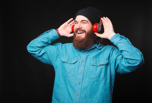 Een vrolijke jonge hipster luistert naar de muziek waar hij van houdt met zijn nieuwe koptelefoon en geniet ervan is wegkijken