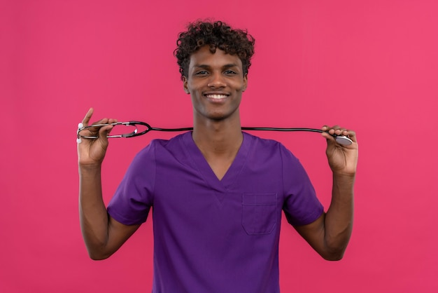 Een vrolijke jonge knappe donkere arts met krullend haar die violette uniforme holdingsstethoscoop met handen draagt