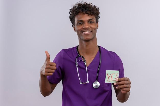 Een vrolijke jonge knappe donkere mannelijke arts met krullend haar draagt violet uniform met een stethoscoop met een papieren kaart met het woord ja met duimen omhoog