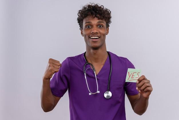 Een vrolijke jonge knappe donkere mannelijke arts met krullend haar in violet uniform met een stethoscoop die een papieren kaart toont met het woord ja