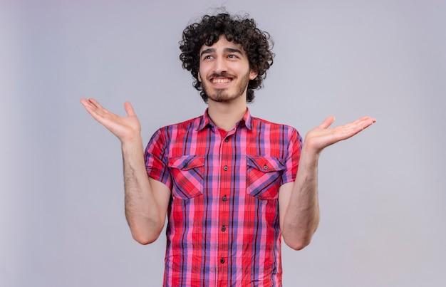 Een vrolijke jonge knappe man met krullend haar in een geruit overhemd dat handen opent