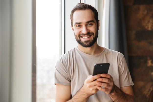 Een vrolijke jonge man binnenshuis thuis chatten via de mobiele telefoon.