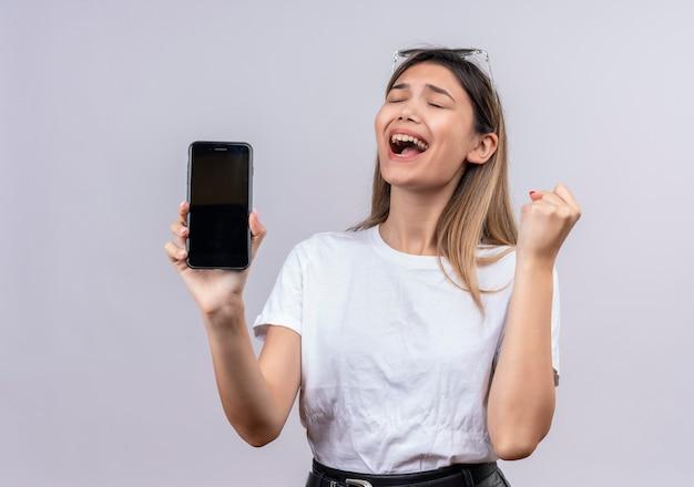 Een vrolijke jonge vrouw in een wit t-shirt met een zonnebril glimlachend terwijl het tonen van lege ruimte van de mobiele telefoon met gebalde vuist op een witte muur