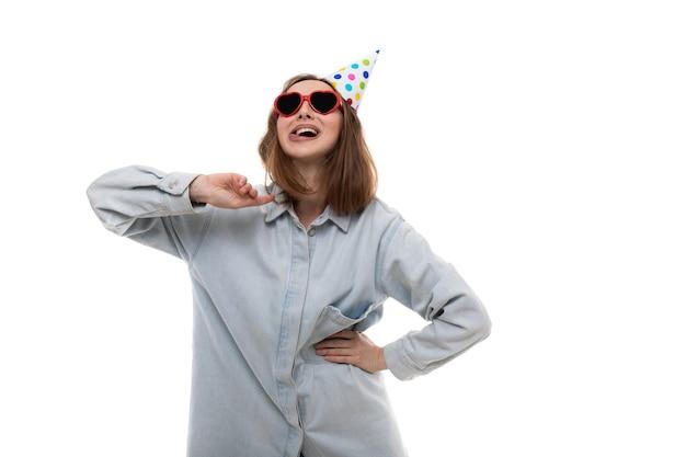 Een vrolijke jonge vrouw in glazen en een feestelijke hoed vormt op een witte achtergrond