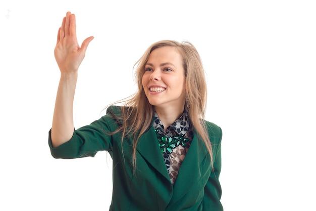 Een vrolijke jonge vrouw in groen jasje kijkt weg glimlachend en realiseerde hand omhoog geïsoleerd op witte muur