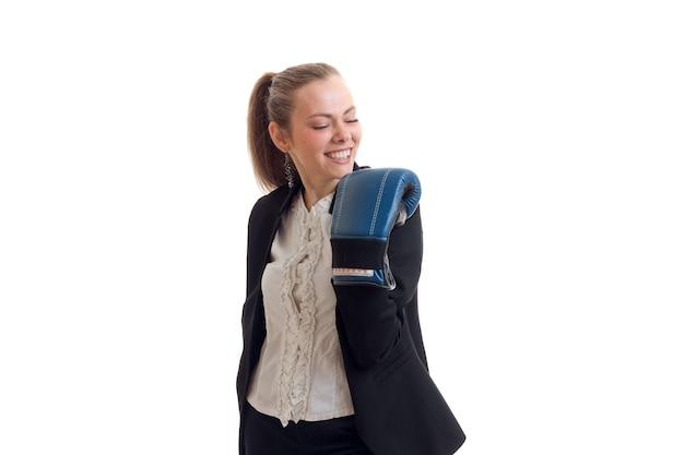 Een vrolijke jonge vrouw in kostuum houdt een hand in bokshandschoen die op witte muur wordt geïsoleerd