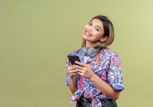 Een vrolijke jonge vrouw in paisley gedrukt overhemd met hoofdtelefoons die mobiele telefoon vasthoudt
