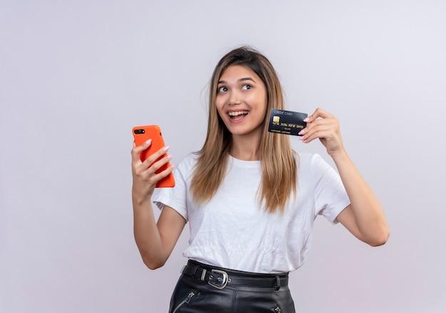 Een vrolijke jonge vrouw in wit t-shirt met creditcard terwijl ze mobiele telefoon vasthoudt op een witte muur