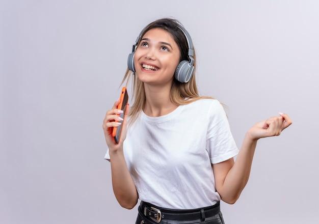 Een vrolijke jonge vrouw in wit t-shirt met koptelefoon zingen terwijl ze luistert naar de muziek op haar telefoon op een witte muur