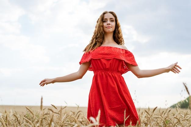 Een vrolijke jonge vrouw met golvend haar in een rode jurk staat overdag in een veld met tarwe tegen een blauwe lucht