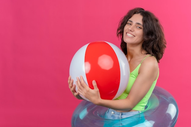 Een vrolijke jonge vrouw met kort haar in een groene crop top glimlachend en met opblaasbare bal
