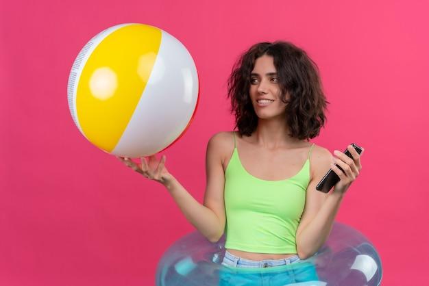 Een vrolijke jonge vrouw met kort haar in een groene crop top kijken naar opblaasbare bal met mobiele telefoon