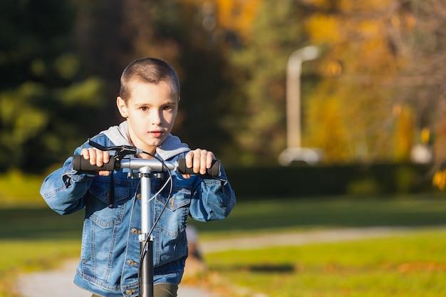 Een vrolijke jongen in een spijkerjasje rolt snel op een scooter in een stadspark