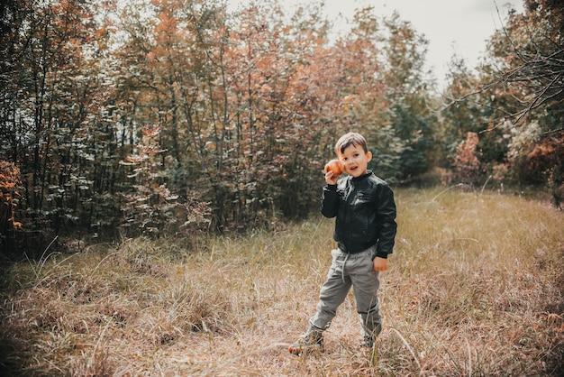 Een vrolijke jongen in het herfstbos met een appel in zijn handen