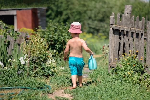 Een vrolijke jongen met een gieter gaat op blote voeten door de tuin om de bloemen water te geven.