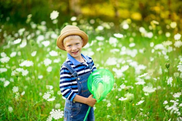 Een vrolijke jongen met een hoed loopt door een veld met bloemen en vangt vlinders met een net