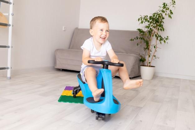 Een vrolijke jongen rijdt thuis in de woonkamer in een blauwe auto
