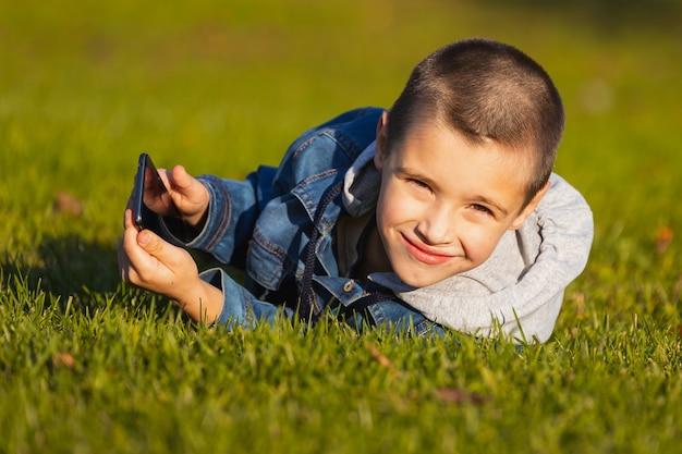 Een vrolijke jongen speelt met een smartphone in een stadspark.