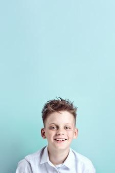 Een vrolijke jongen staat en glimlacht in een licht overhemd op een fel gekleurde muur