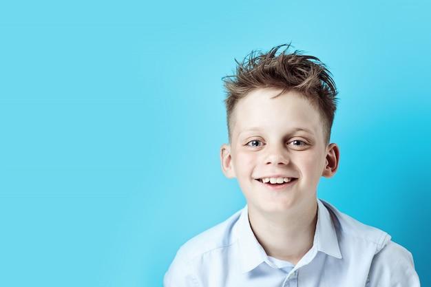 Een vrolijke jongen staat en glimlacht in een licht shirt