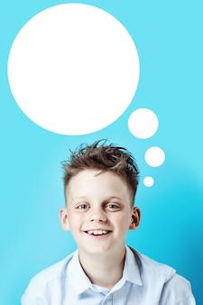 Een vrolijke jongen staat op en glimlacht in een licht shirt op een felgekleurde