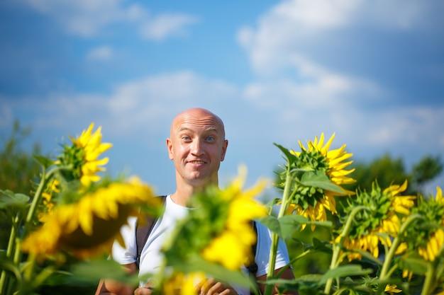 Een vrolijke kale man in een veld met bloeiende gele zonnebloemen tegen een blauwe hemel staat lachend